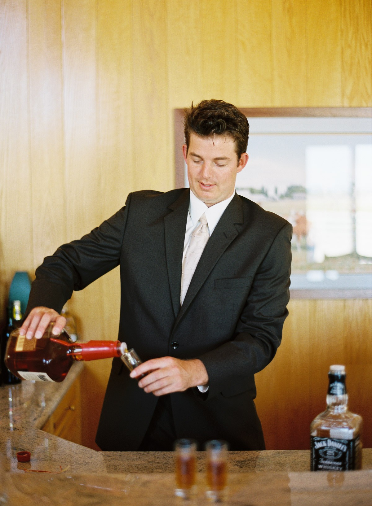 Groomsman pouring a drink