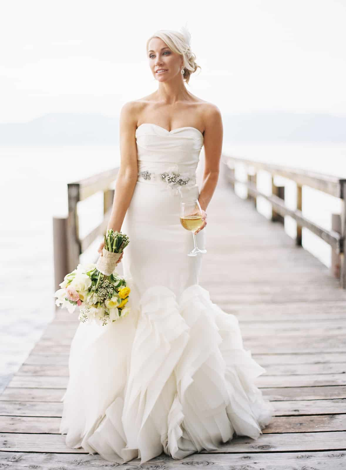 Bride in Vera Wang dress wtih white rose bouquet drinking white wine