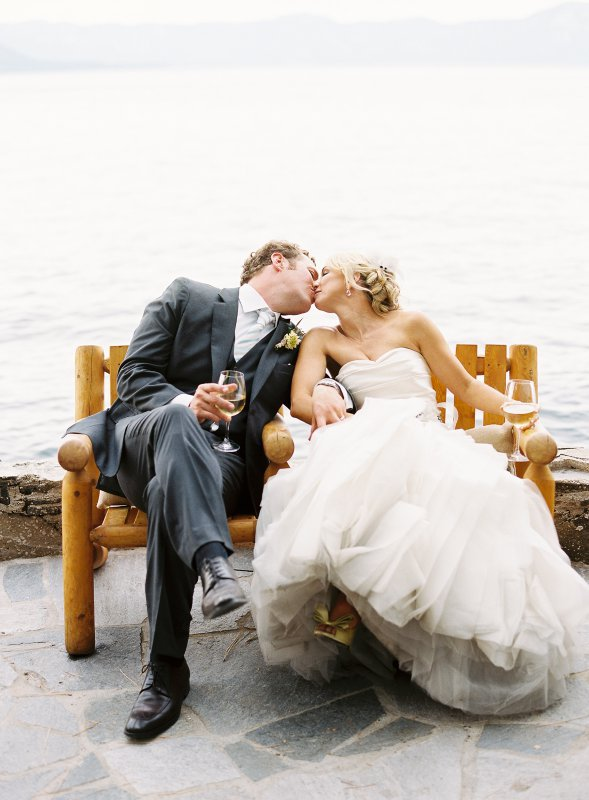 Married couple kissing beside Lake Tahoe