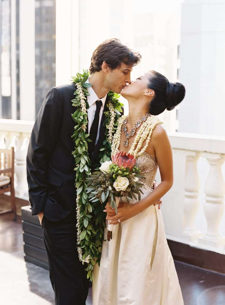 Maile ti leaf and white orchid lei and protea bouquet