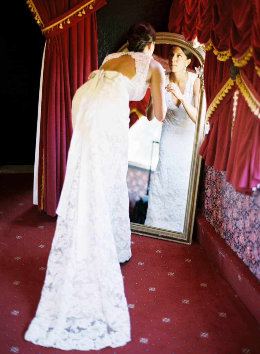 Bride checking her makeup in the mirror with red drapes