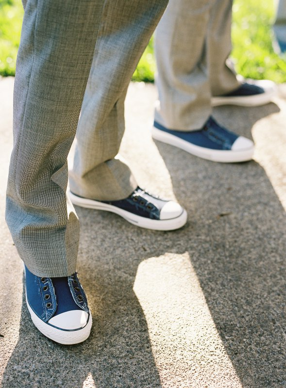 Closeup of groomsmen's blue converse shoes