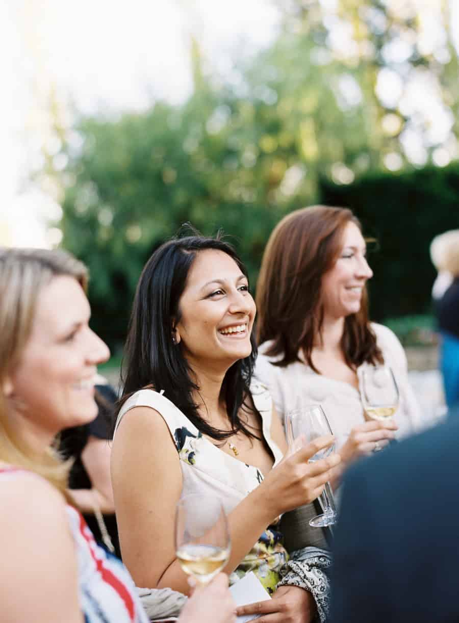 Smiling guests drinking white wine
