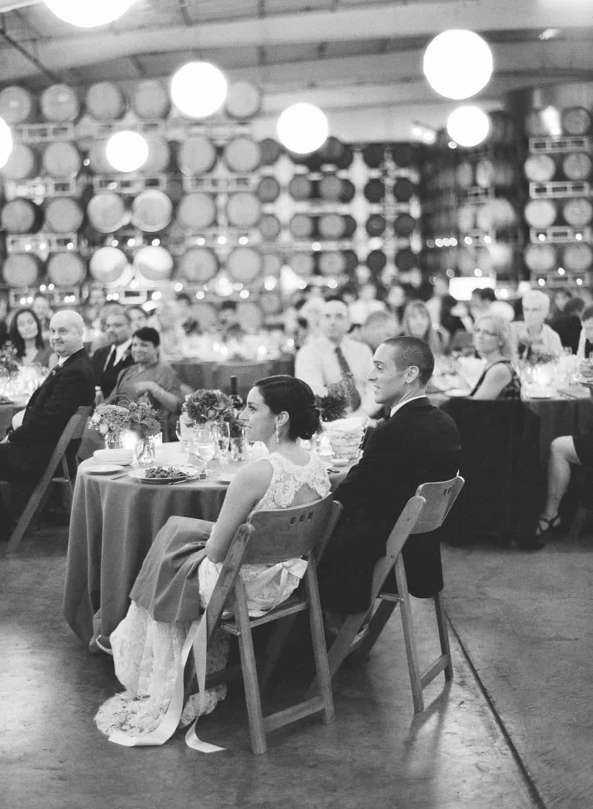 Couple seated at the head table with wine barrels in the background