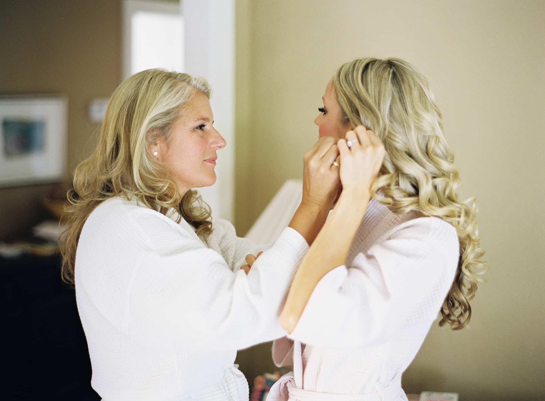 Mother puting earrings on bride