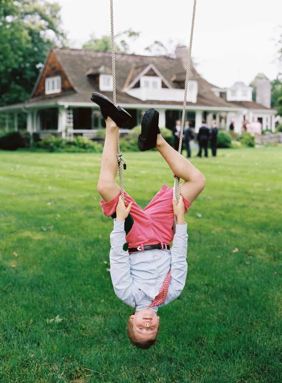 boy upside down on a swing