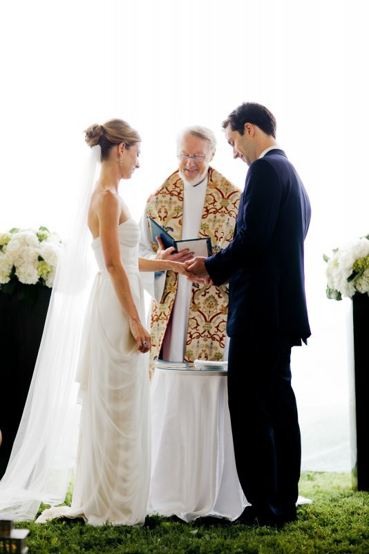 groom placing ring on bride
