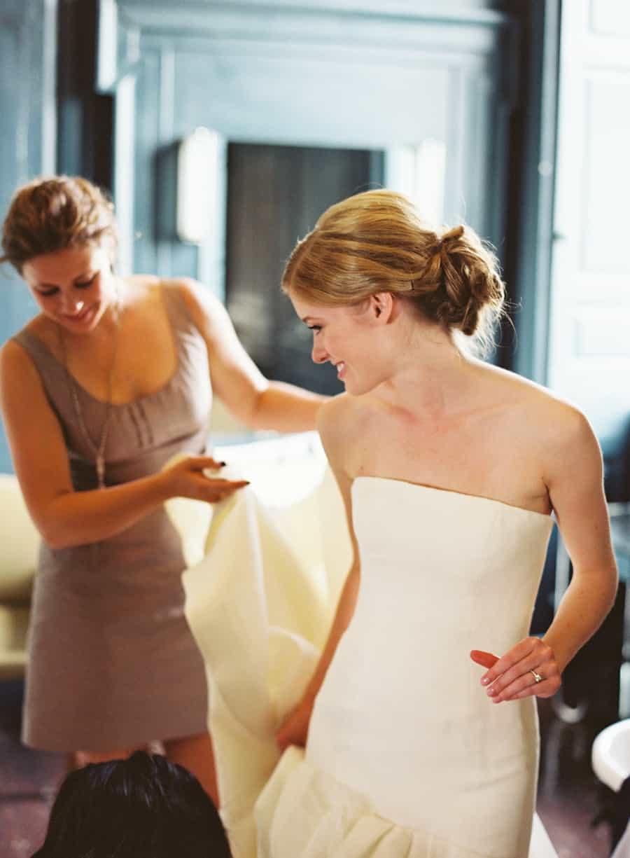 Bride puttign on her dress