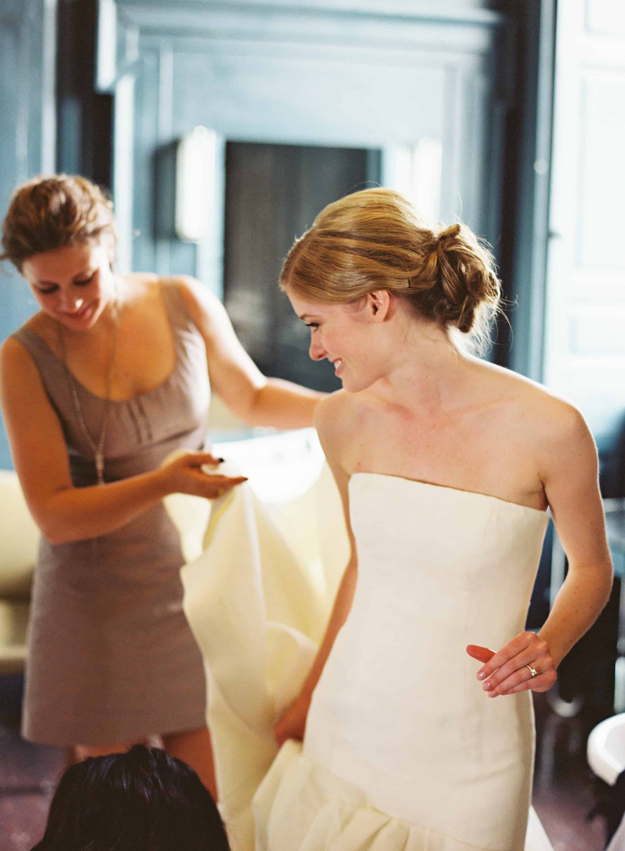 Bride puttign on her dress