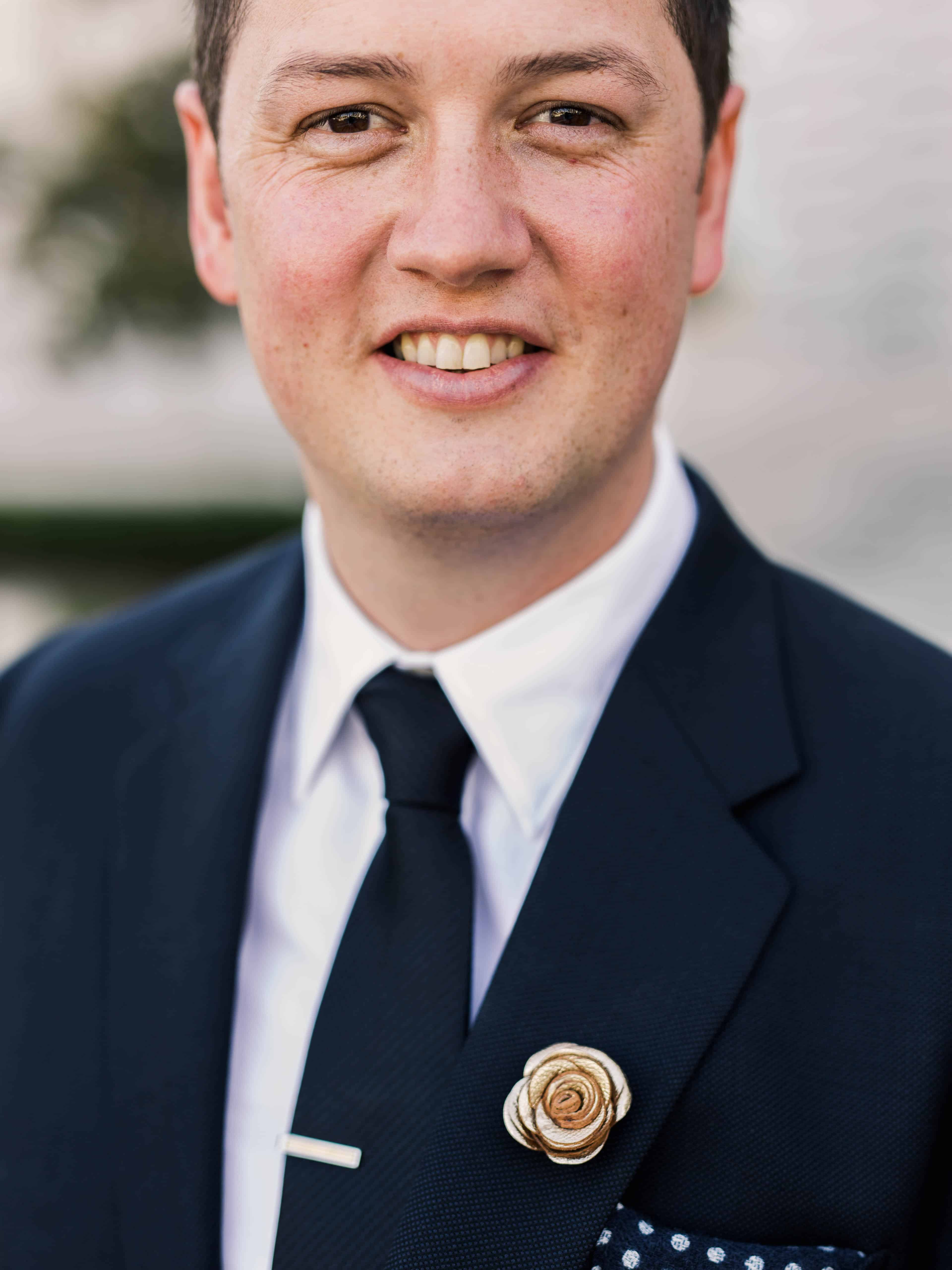 groom portrait with gold leather boutonniere