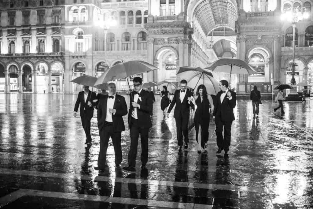 Guests at black tie gay destination wedding walking across Piazza del Duomo in Milan Italy