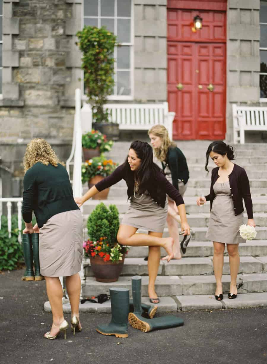 Bridesmaids putting on wellies