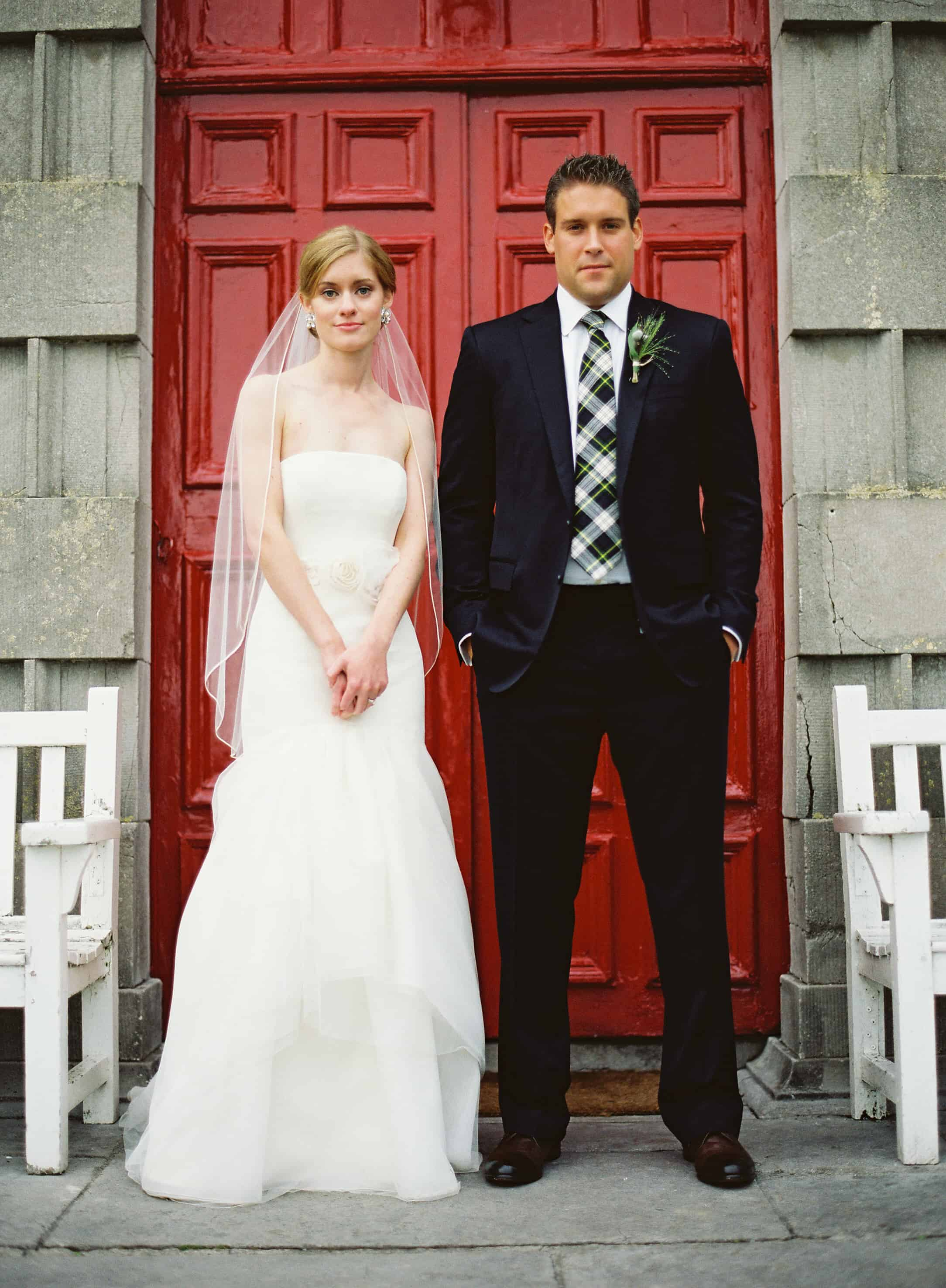 Bride and groom in front of a red door