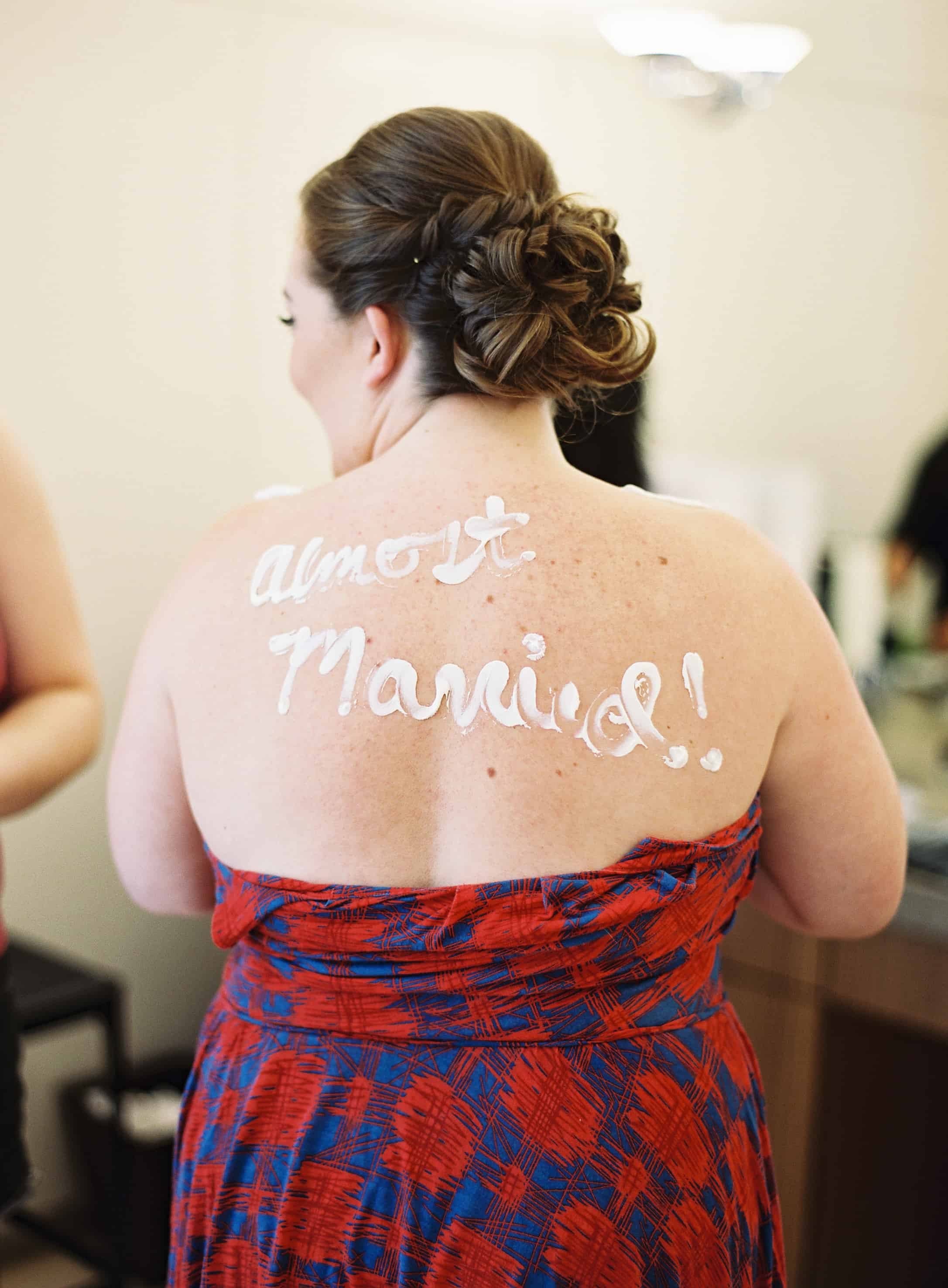 almost maried lotion writing on bride's back