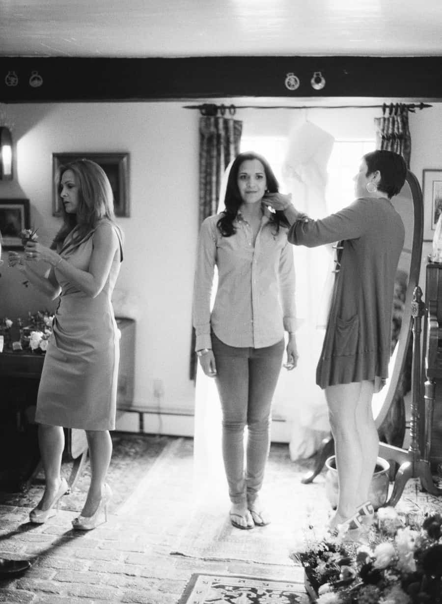bride standing and getting hair done