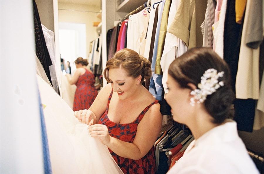 bride looking at dress in closet