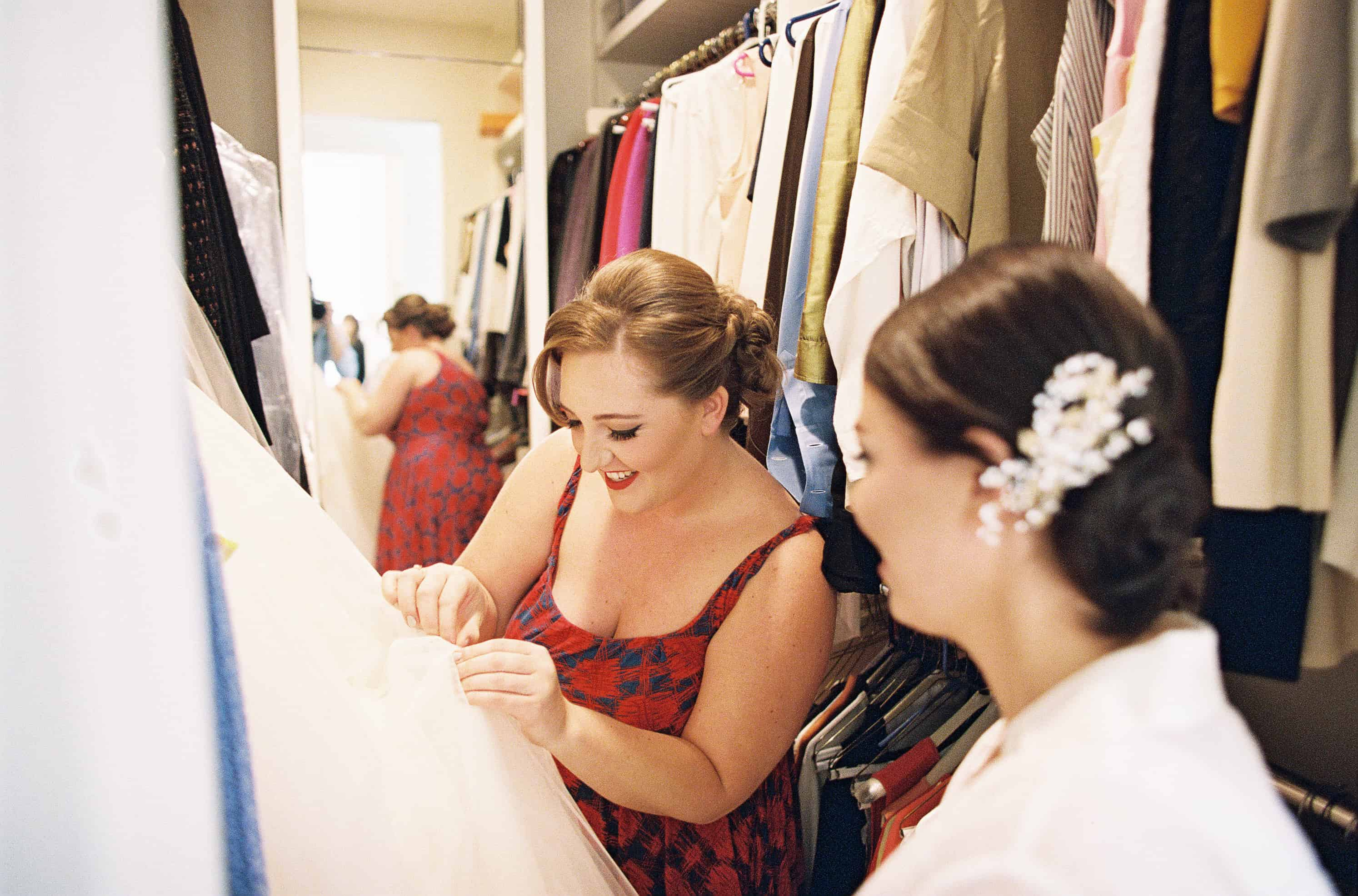 bride looking at dress in closet