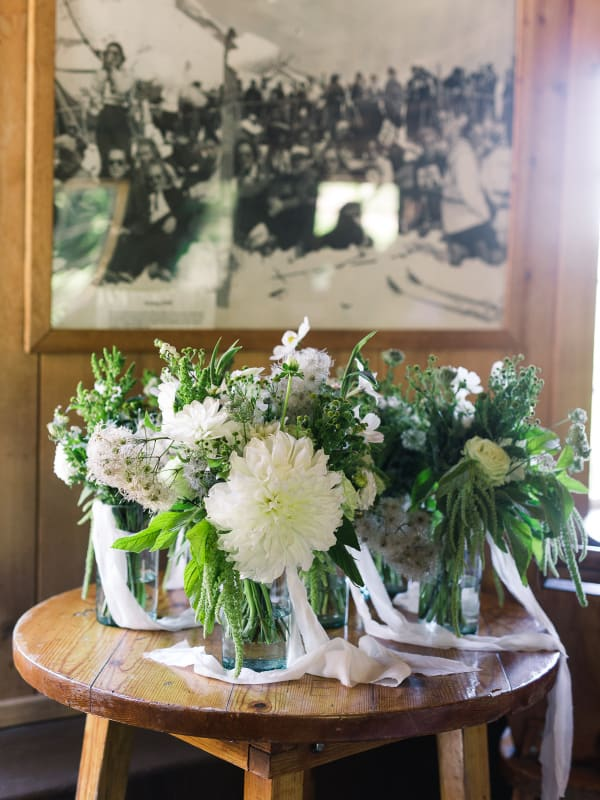 bouquets in vases on wood table with old framed photo