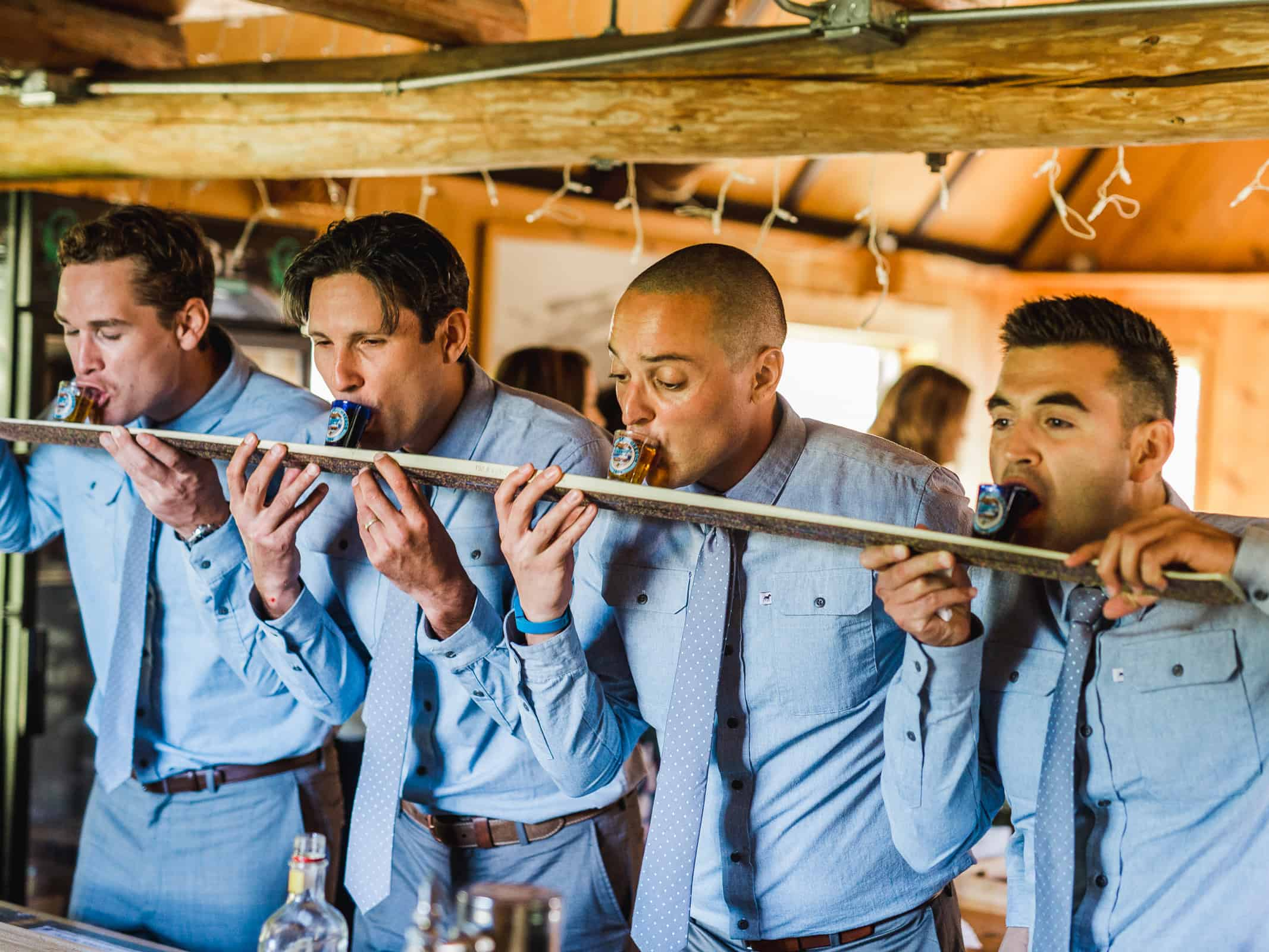 groomsmen drinking from a shot ski