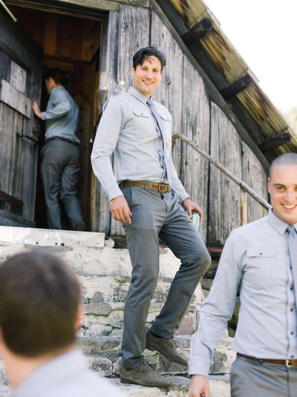 groomsmen in gray walking down warming hut stone steps