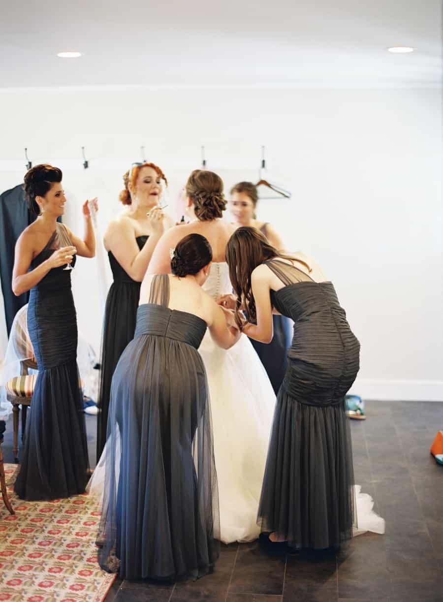 bridesmaids getting bride into dress