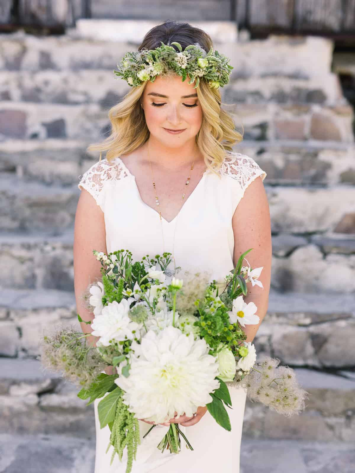 bride portrait with flower crown and bouquet in front of stone steps