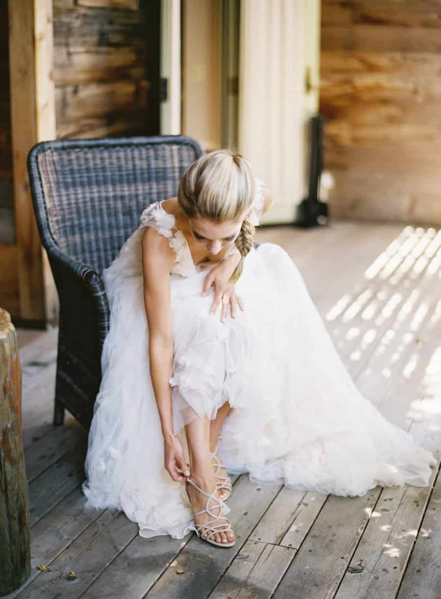 bride sitting and putting on shoes