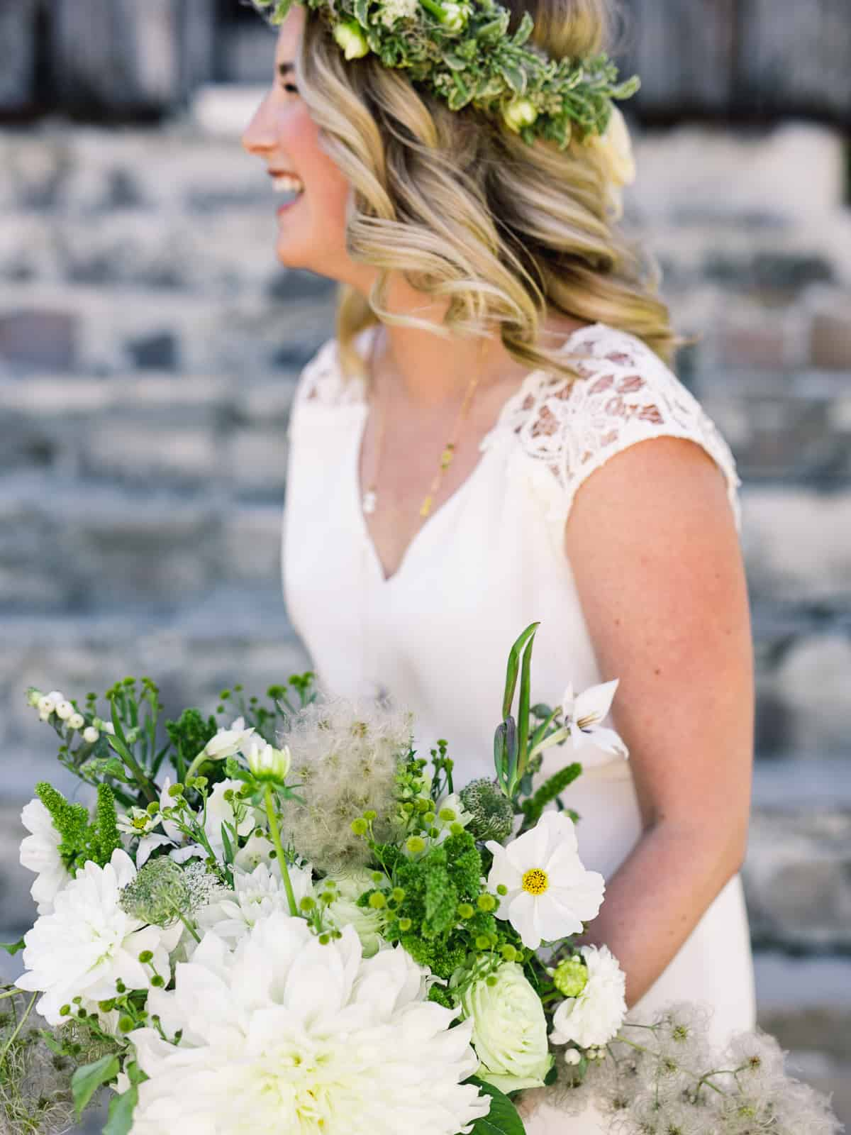 bride laughing with green and white bouquet