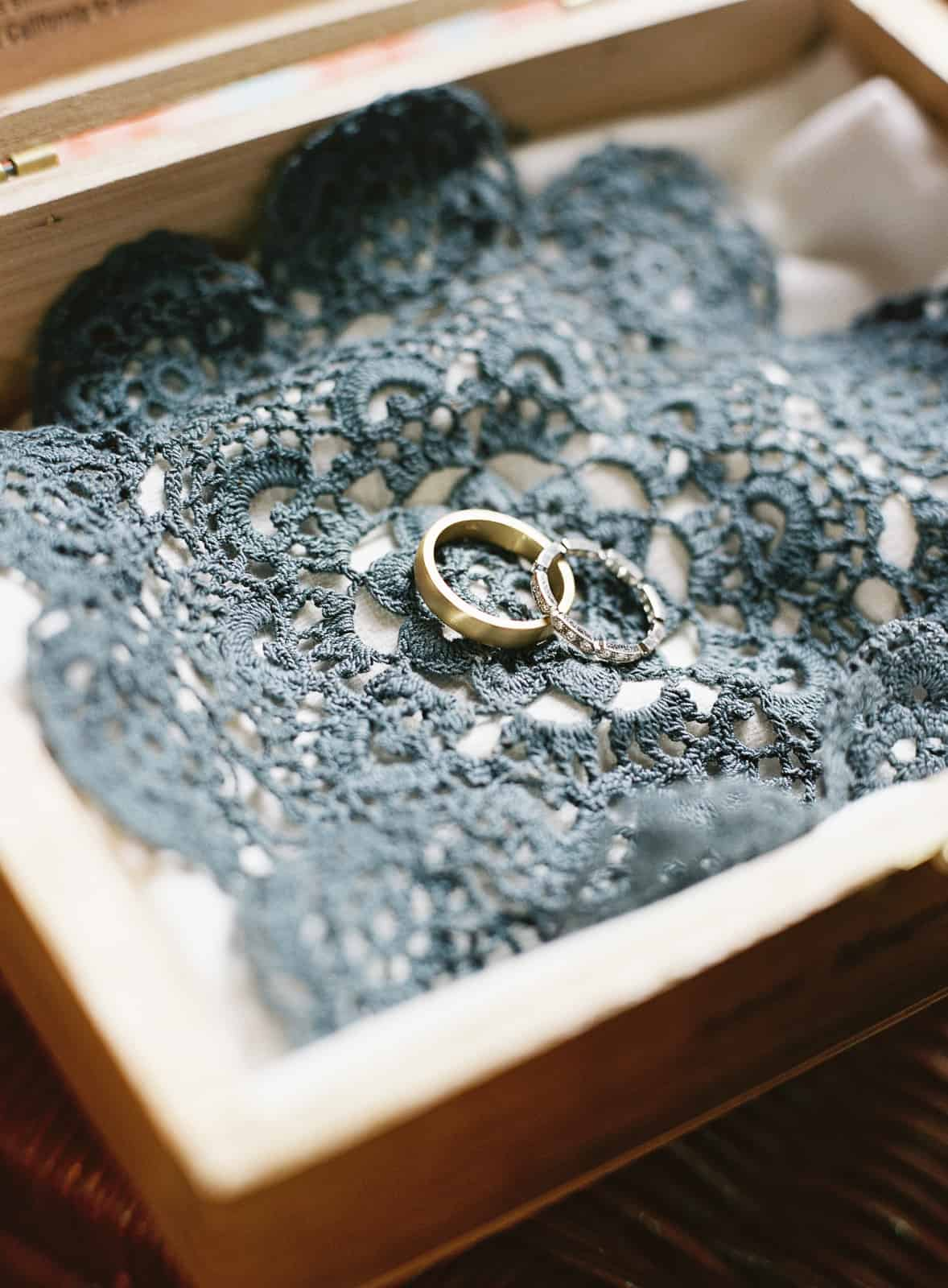 rings on blue doily in wood box