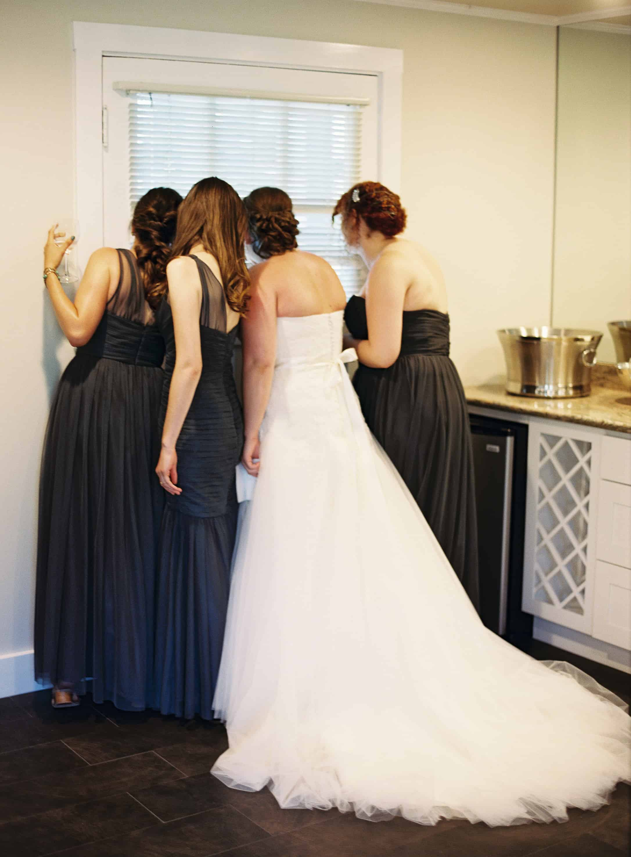 bride and bridesmaids peeking out window