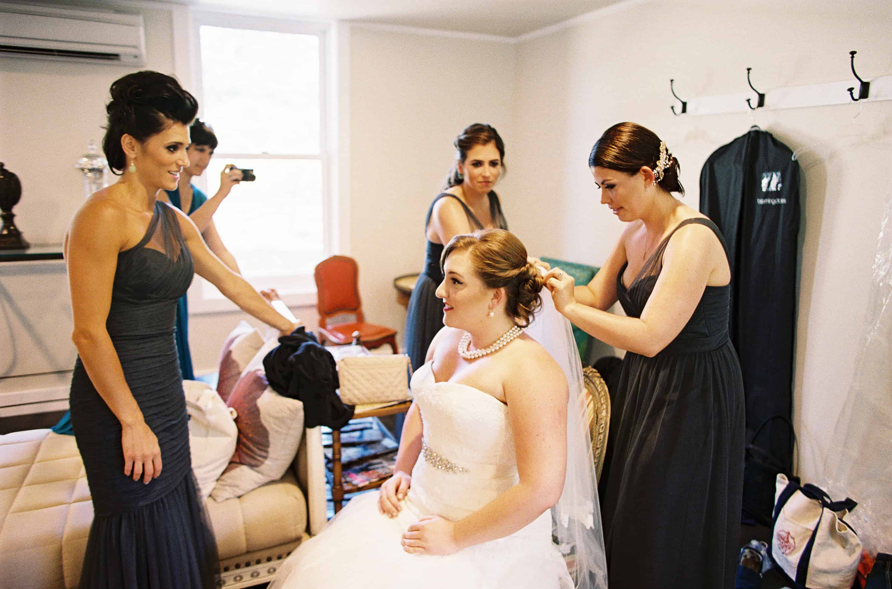 bride and bridesmaids putting veil on