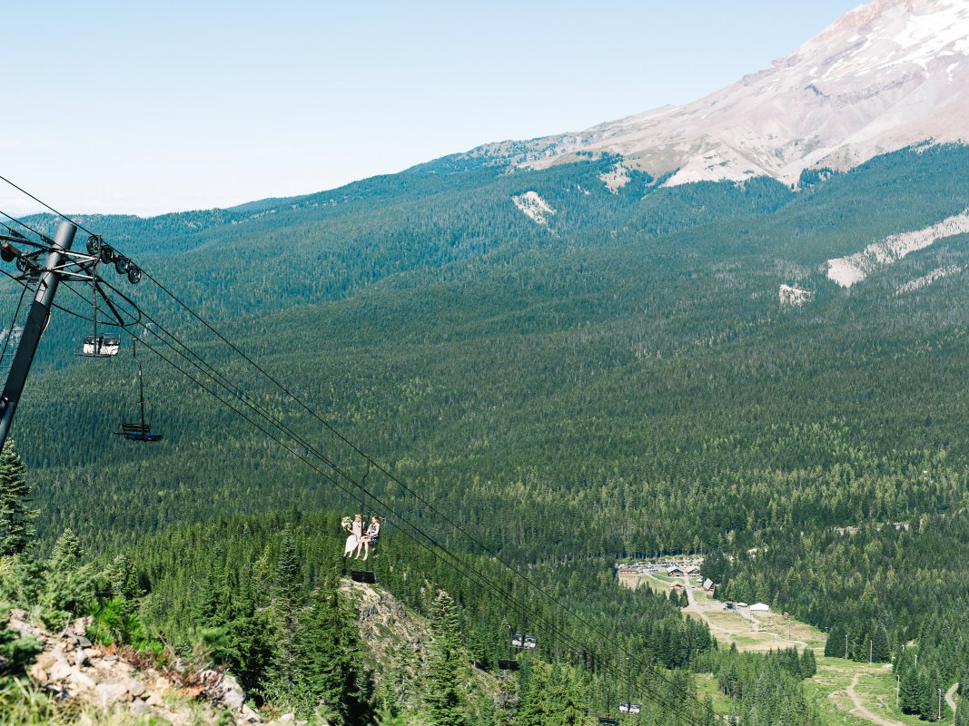 bride and bridesmaid on chairlift with trees and mountain in background