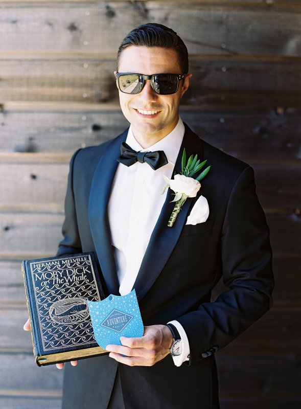 black tie groom with moby dick book gift from bride