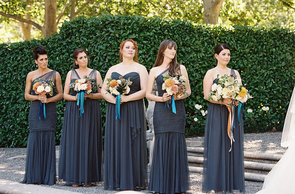 bridesmaids in gray dresses holding orange and white bouquets