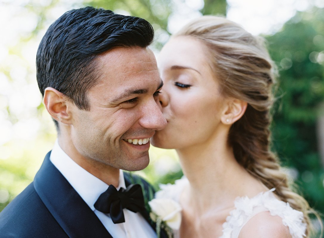 groom wearing tuxedo getting a kiss on the cheek from bride