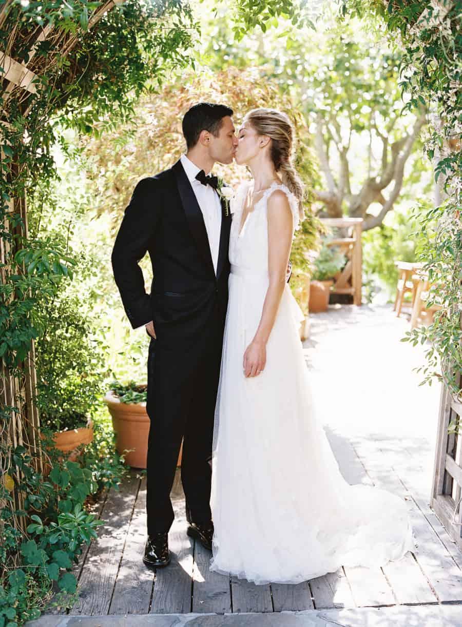 bride and groom kiss under trellis