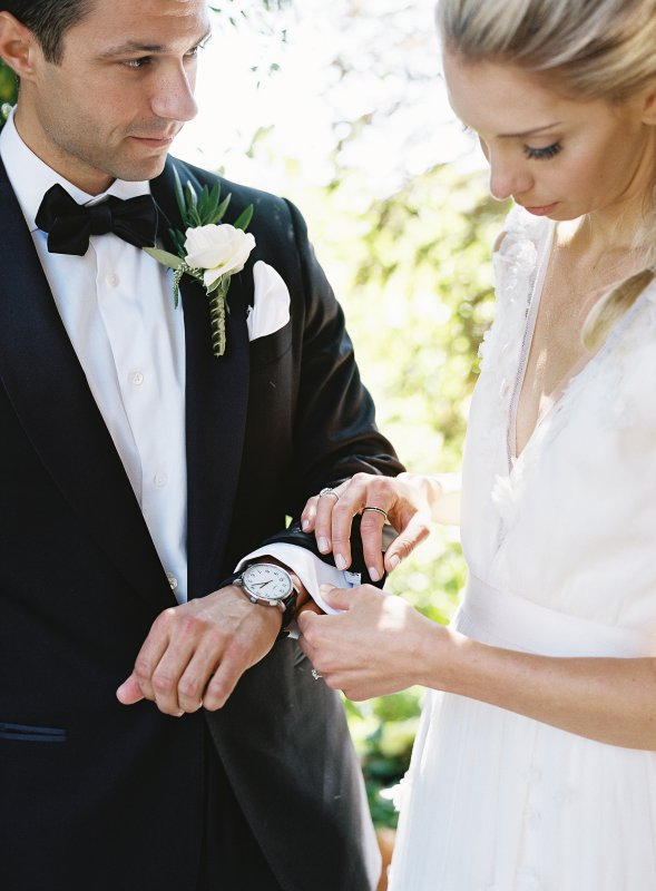 bride helping groom with cufflink