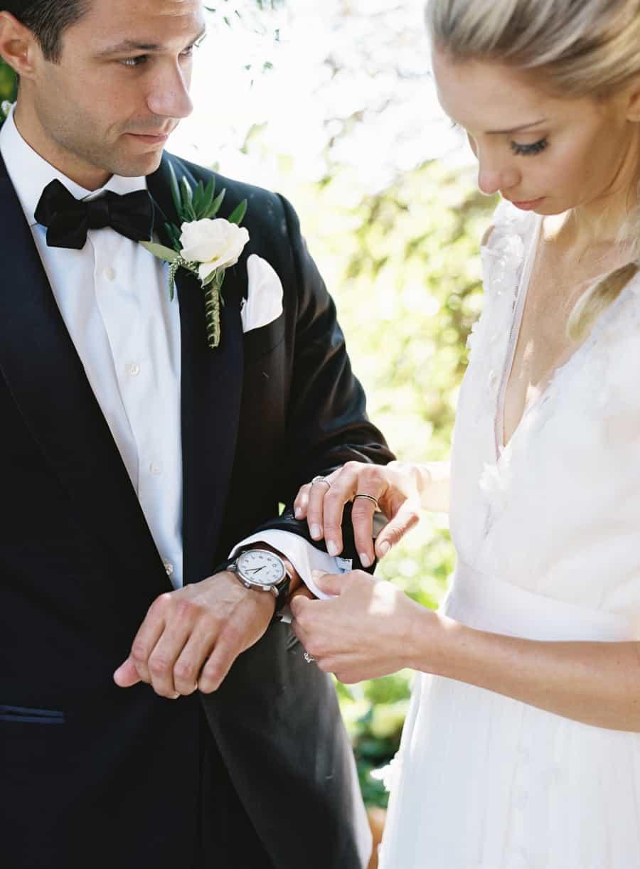 bride helping groom with cufflink