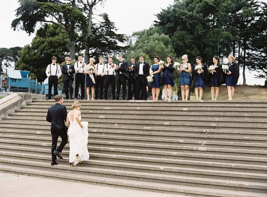 bride and groom walking up steps to wedding party