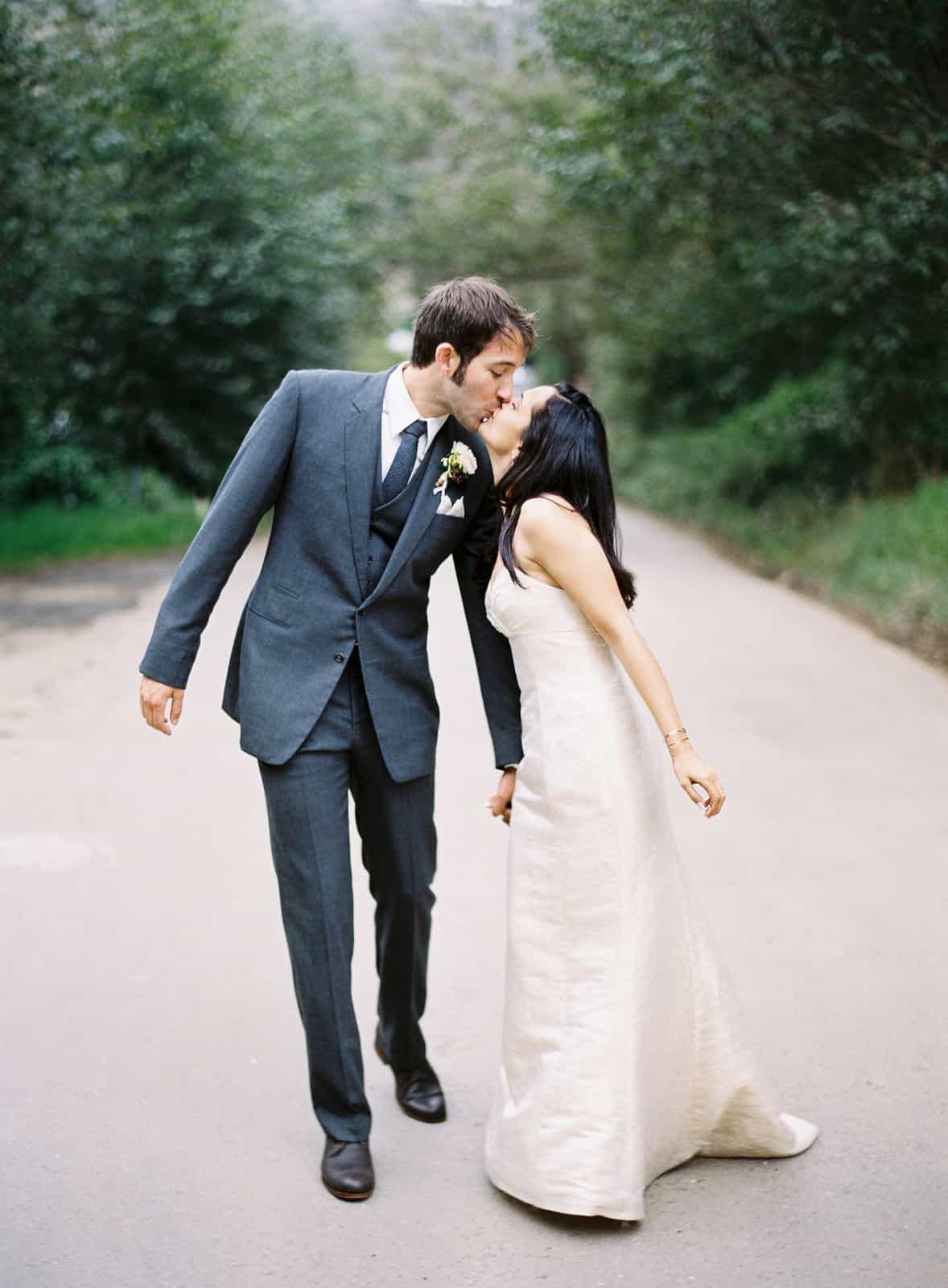 married couple kissing and walking