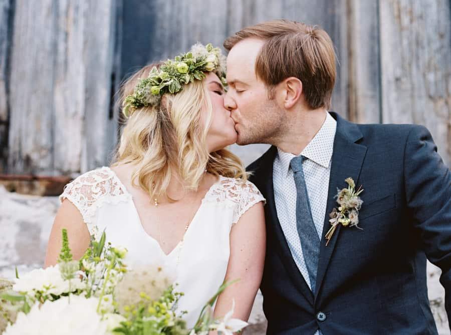 bride and groom kissing behind warming hut