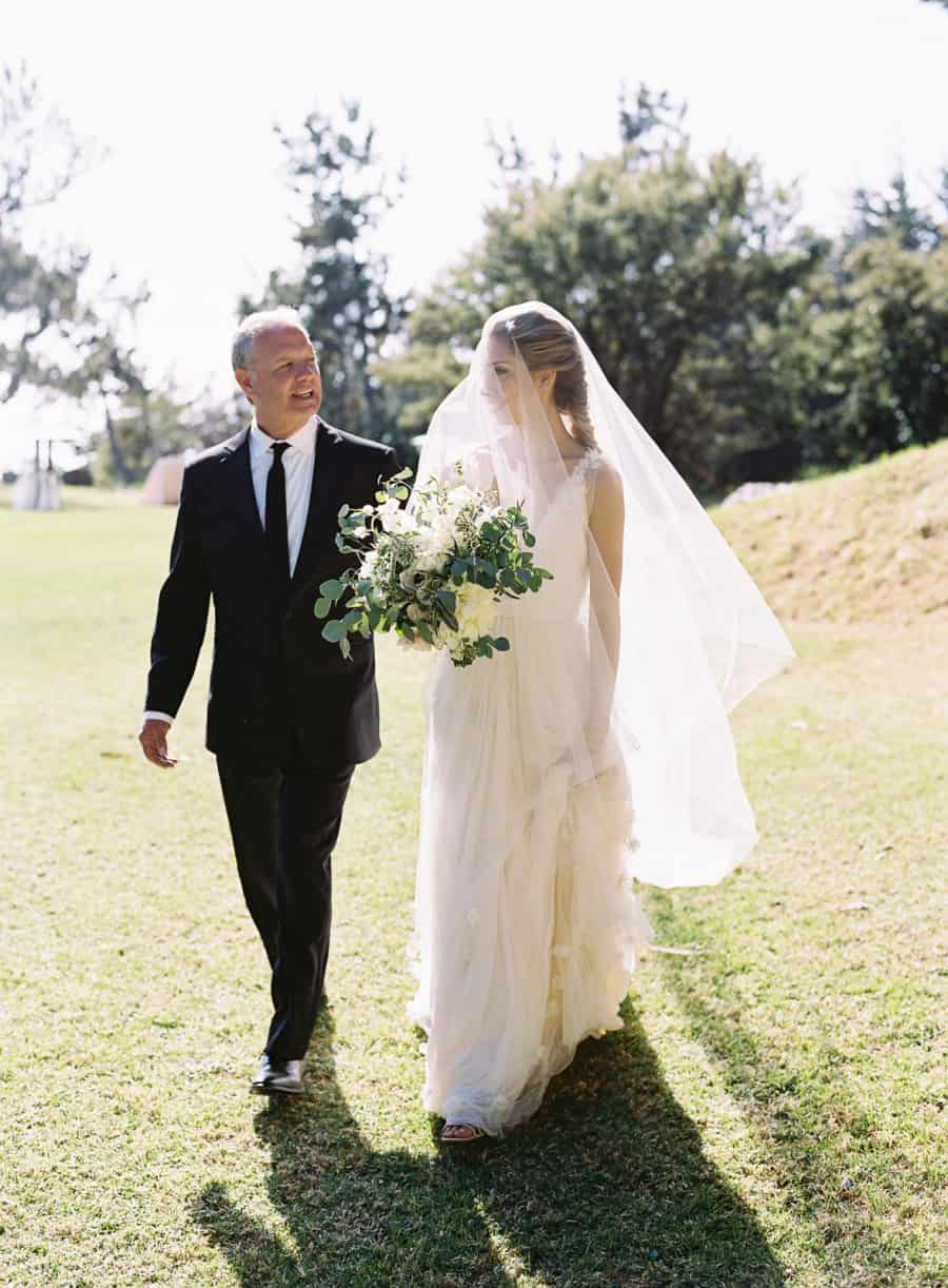 bride in veil walking with her father