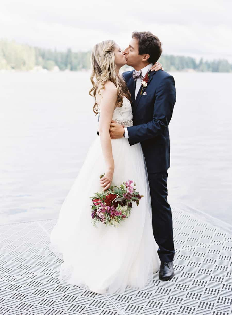 married couple kissing on dock