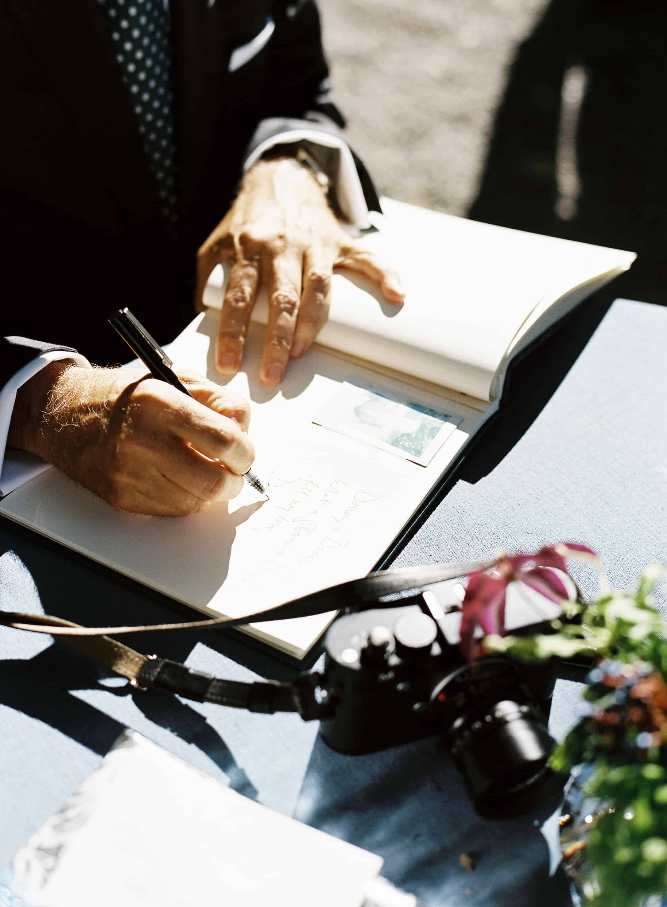 signing guest book with leica camera