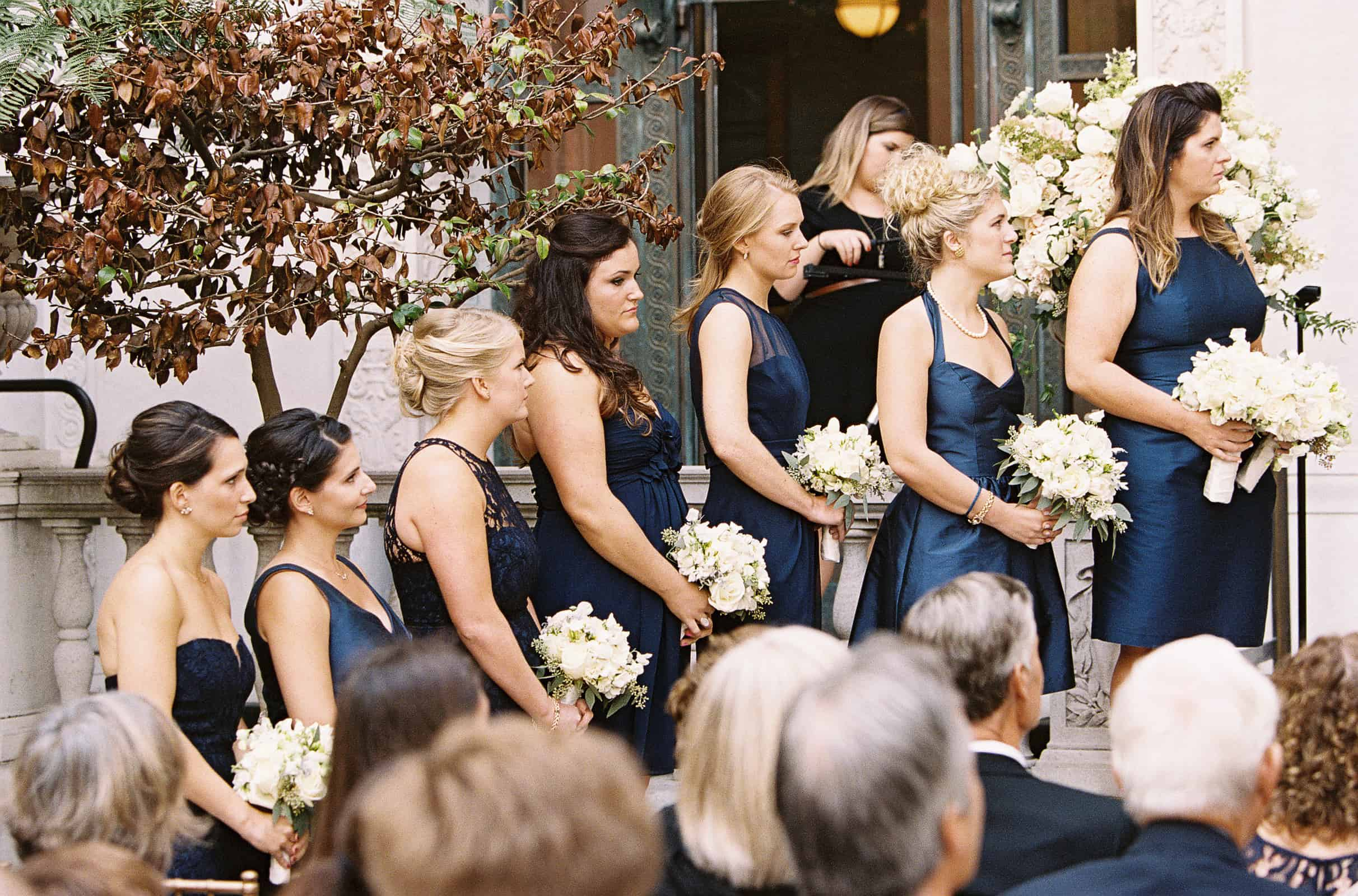 bridesmaids in navy blue dresses in a line