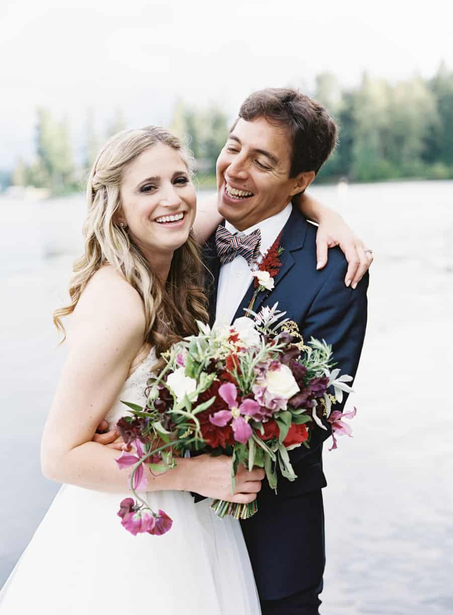 laughing bride and groom with purple bouquet