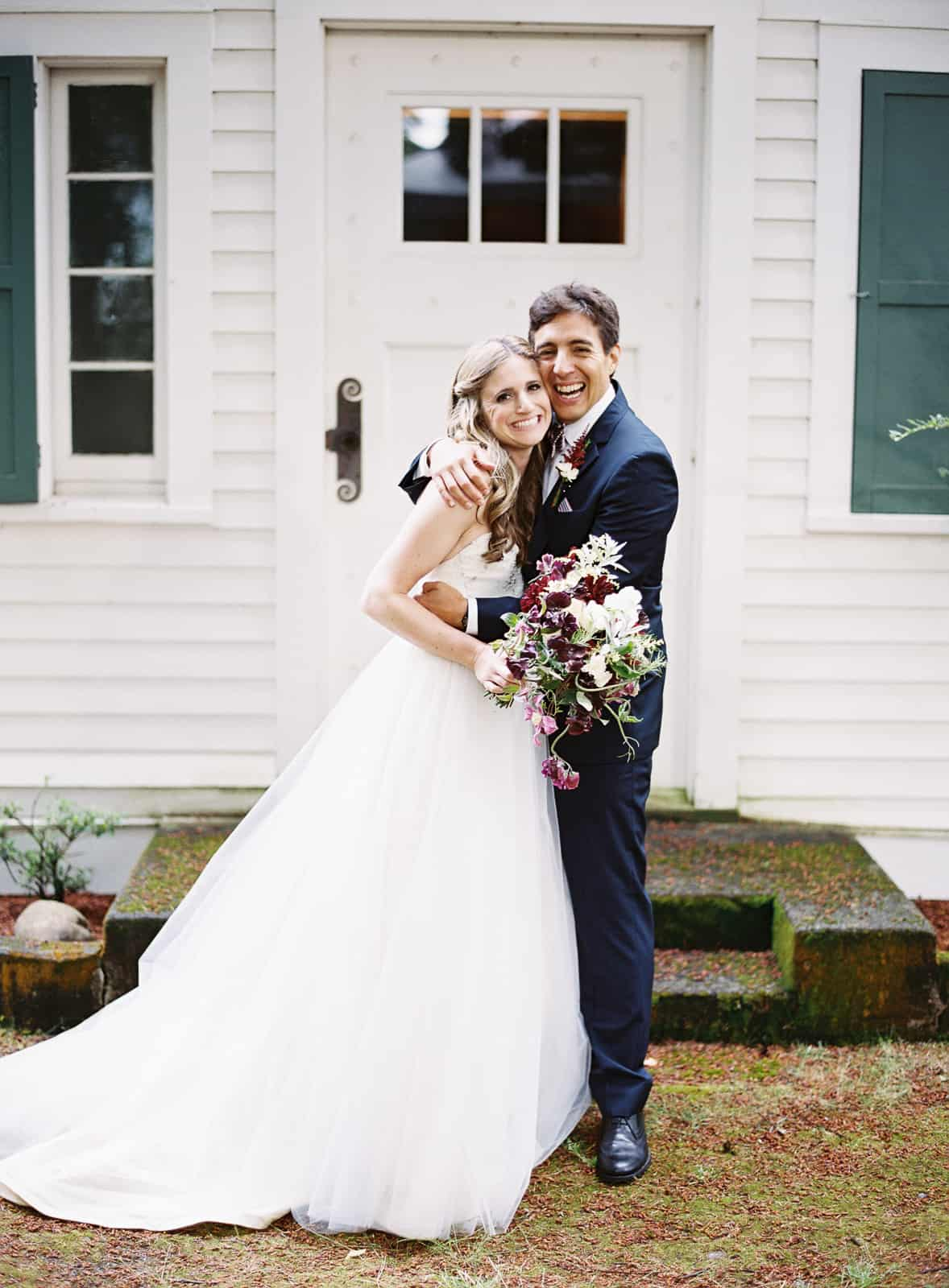 bride and groom in front of old cabin