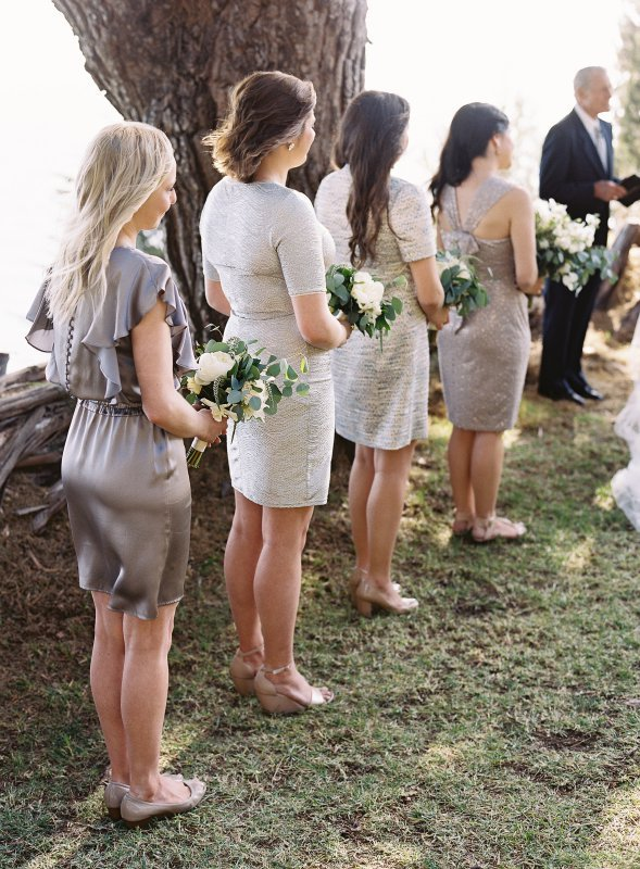 bridesmaids in silver dresses with white and green bouquets lined up