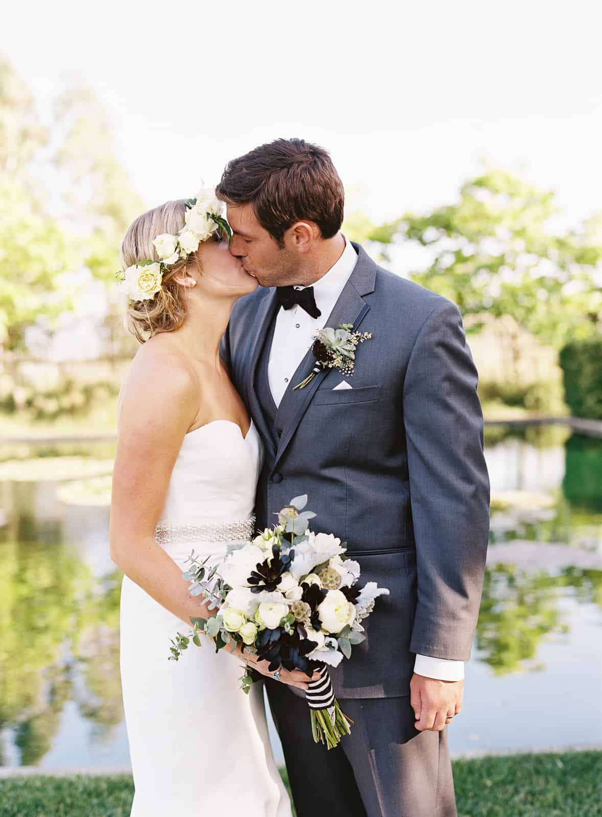 couples portrait kissing by pond