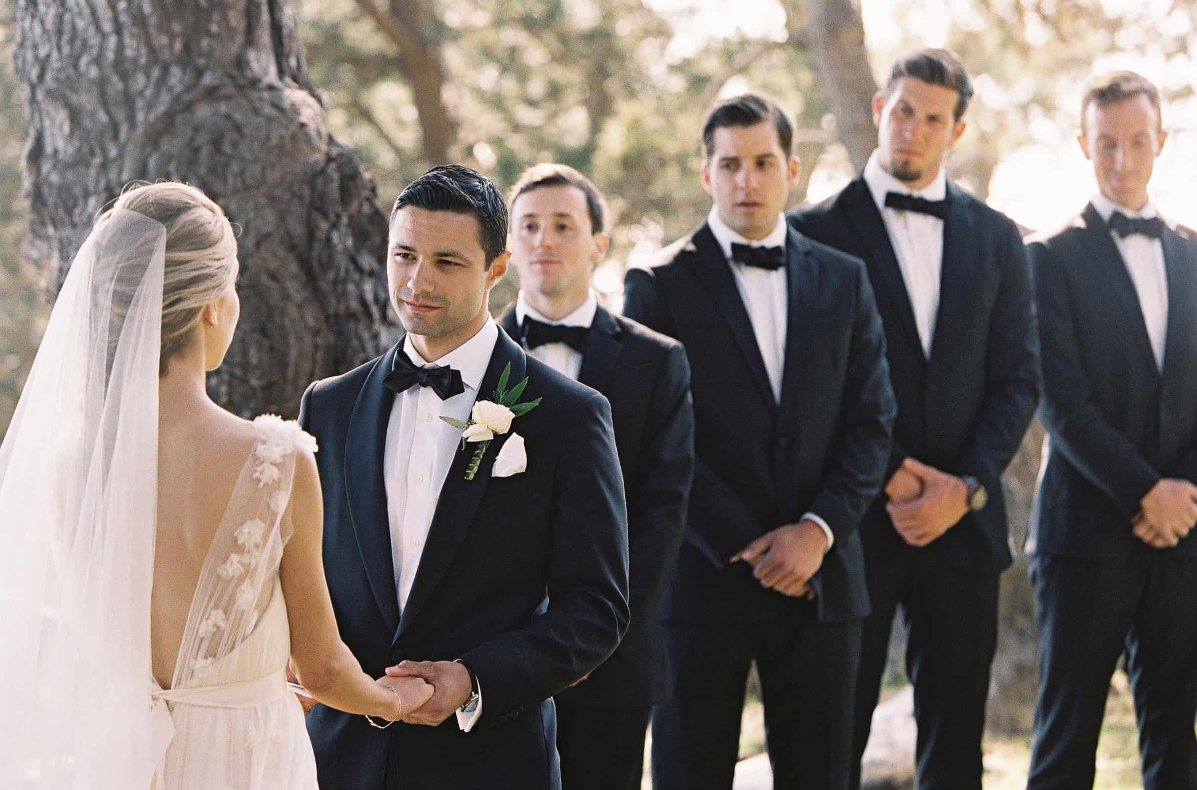 groom looking at bride during the ceremony with black tie groomsmen in background